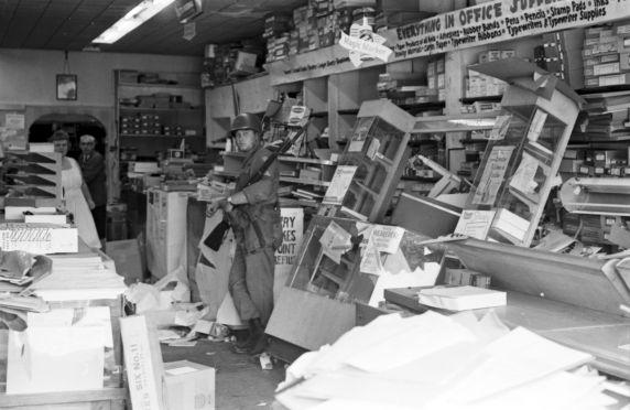 略奪された商店に佇む州兵
